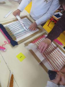 Les enfants utilisent un métier à tisser en carton