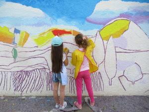 Fillettes qui peignent une fresque dans leur école