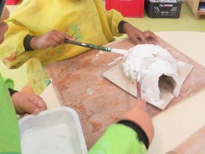 Les enfants peignent leur igloo en blanc